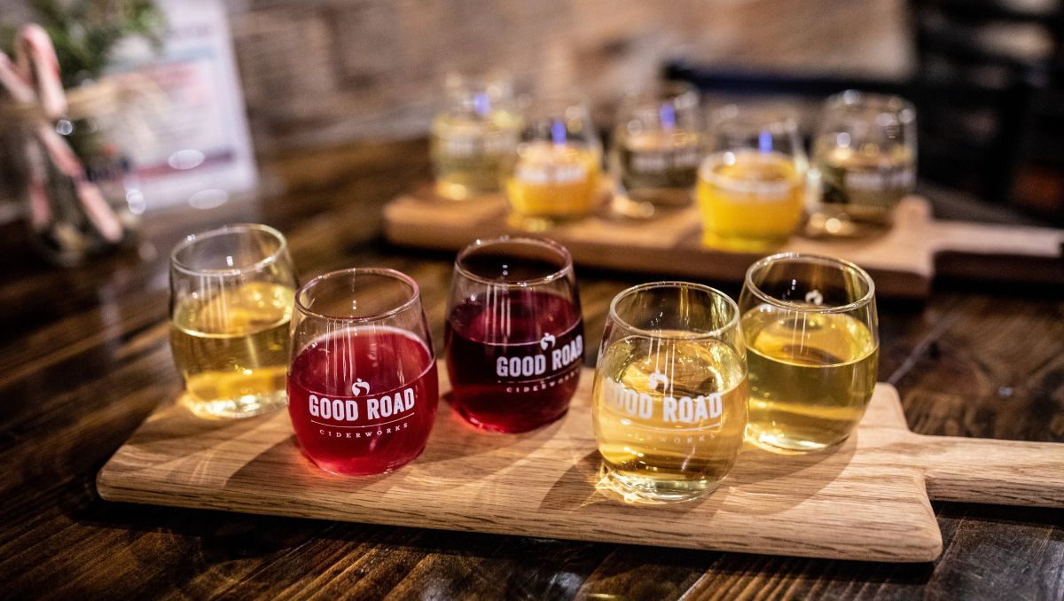 Flight of colorful ciders from GoodRoad CiderWorks sitting on a paddle