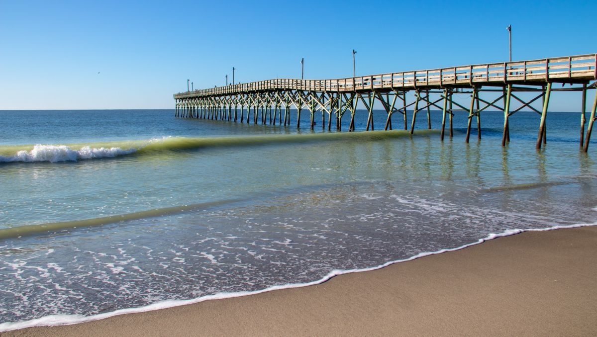 Holden Beach Pier jutting into water during daytime in Brunswick Islands