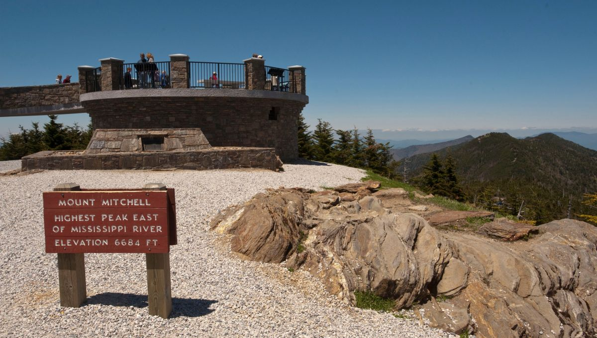 Peak of Mount Mitchell with lookout tower and sign on sunny day