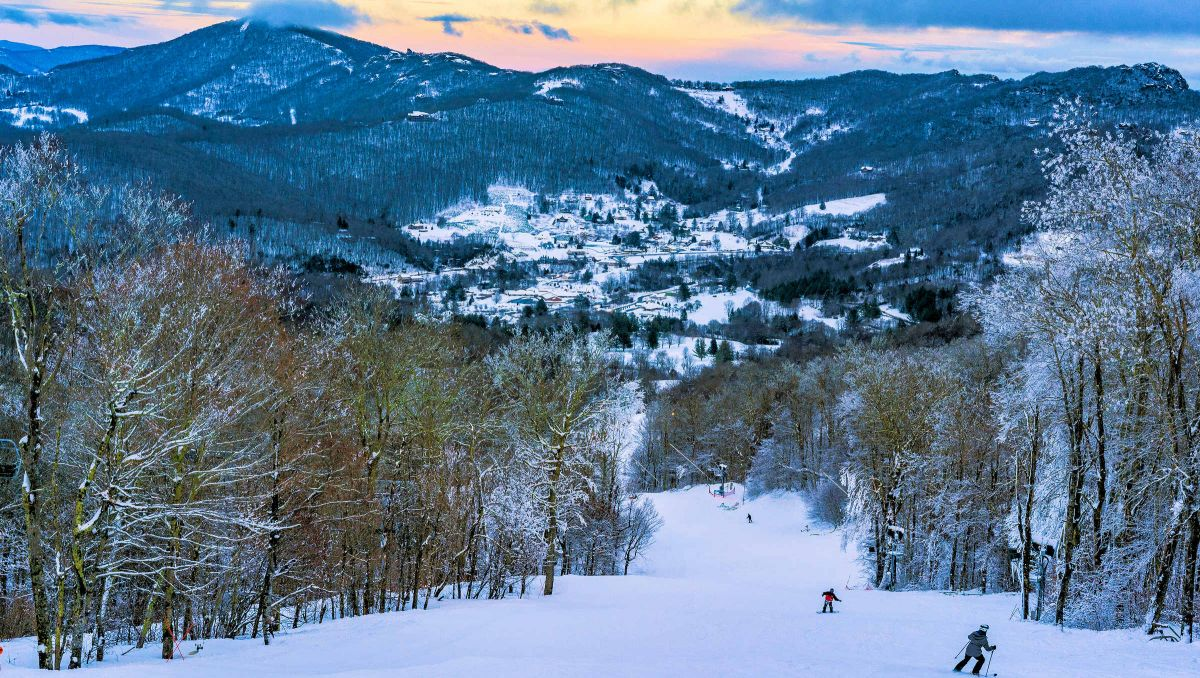 People skiing down hill with wintry trees and mountains during sunset in Sugar Mountain
