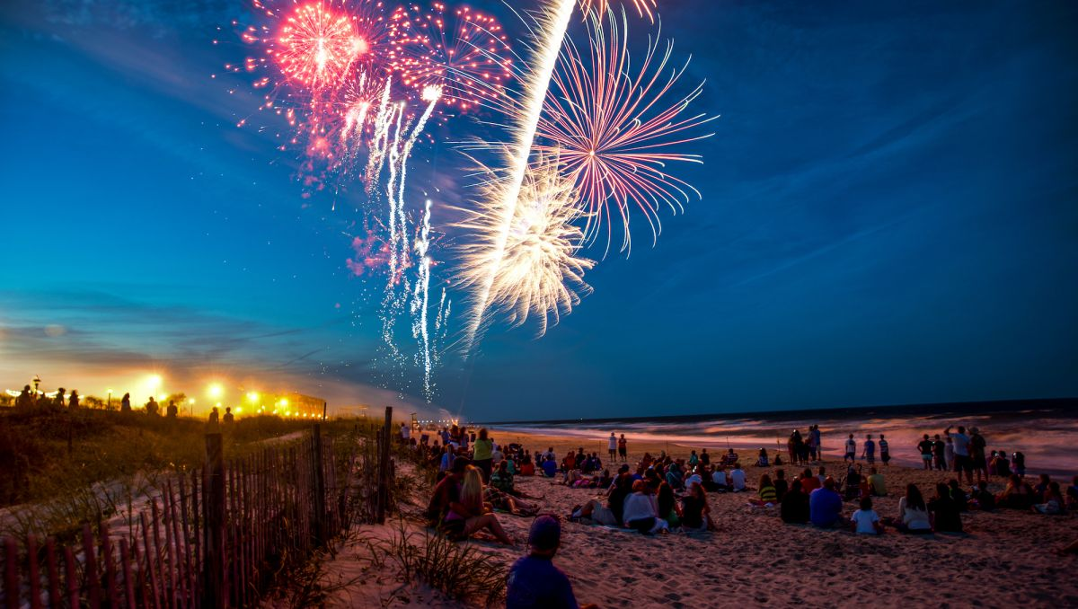People sitting on beach by the ocean watching fireworks in the sky