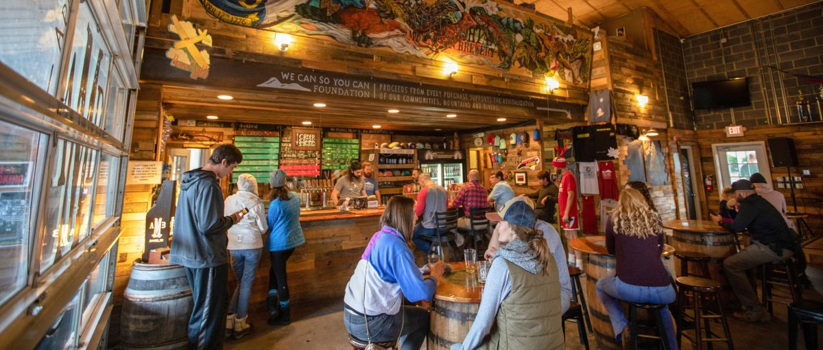 People enjoying beers inside at Appalachian Mountain Brewery, with hand-painted mural above bar