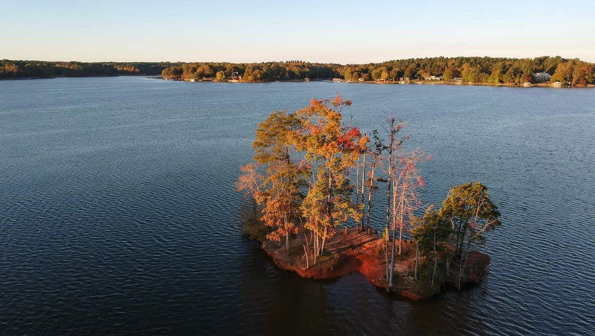 Aerial view of island in Lake Norman and shore in background with fall foliage