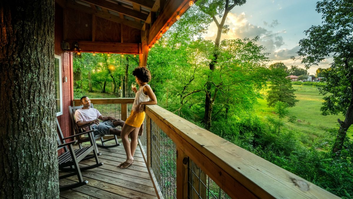 Couple enjoying wine on treehouse balcony with green trees and grounds to the right