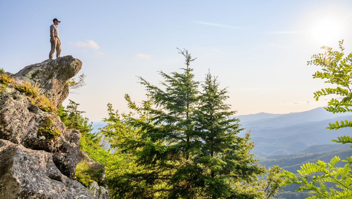 Man standing on top of The Blowing Rock outcropping surrounded by green trees and mountains in background