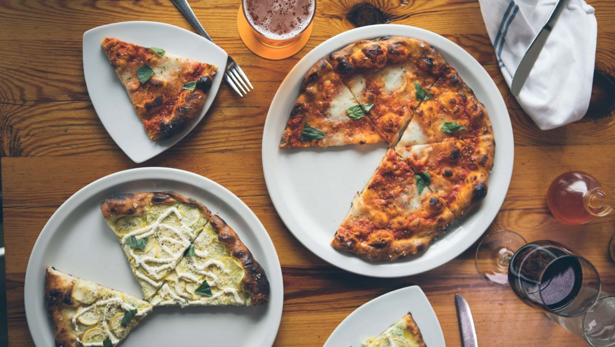 Different pizzas set out on a table with pieces missing