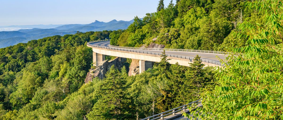 Linn Cove Viaduct surrounded by green trees and mountains in background on clear, bright day