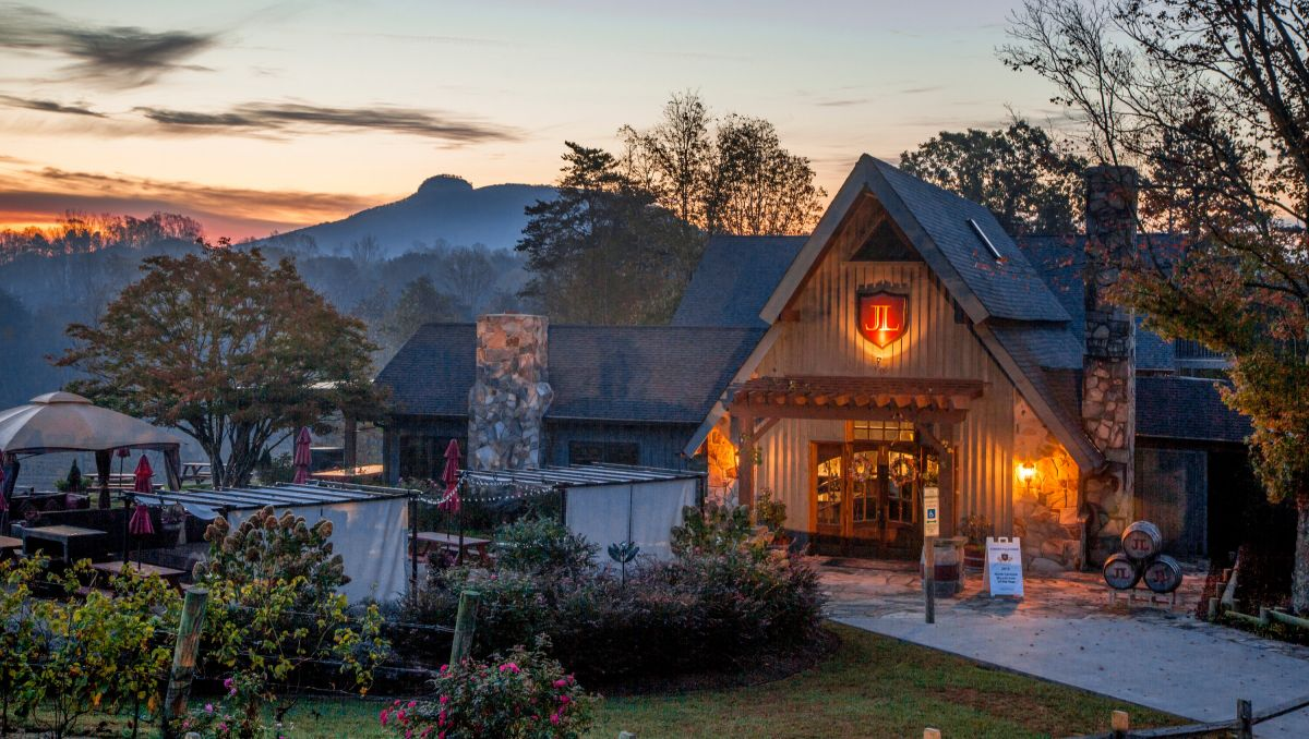 JOLO Winery & Vineyards exterior at dusk with Pilot Mountain is background
