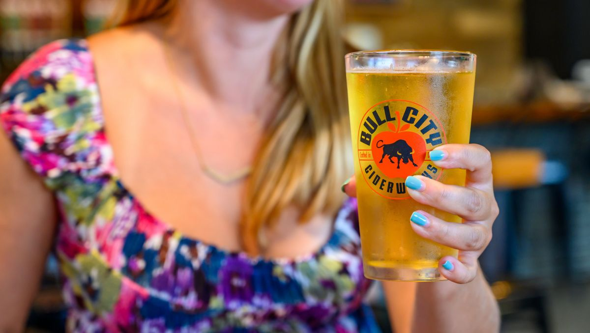 Girl holding pint of cider at Bull City Ciderworks