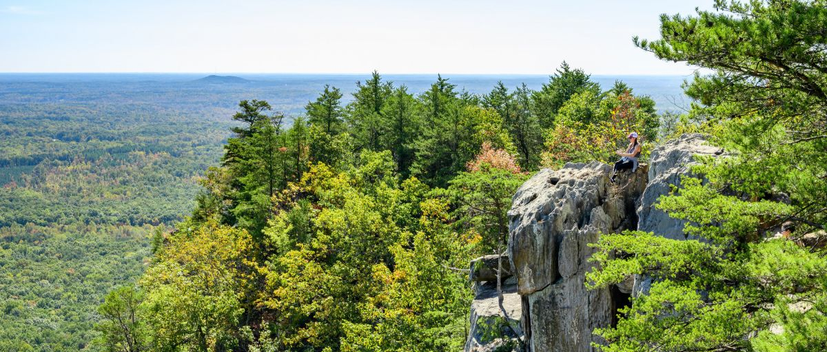 Woman sitting on edge of cliff at Crowders Mountain with trees all around on sunny day