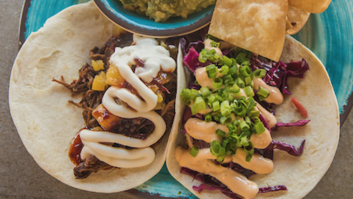 Two tacos side by side on a plate