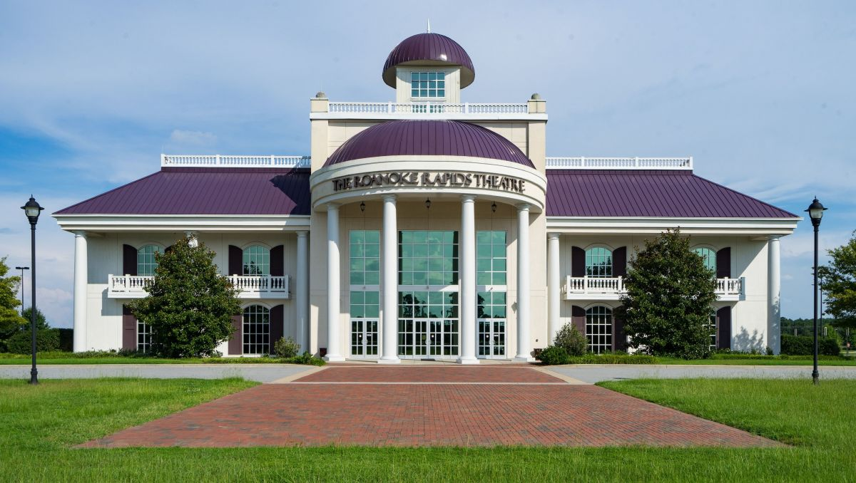 Exterior of Roanoke Rapids Theatre with purple roof during daytime