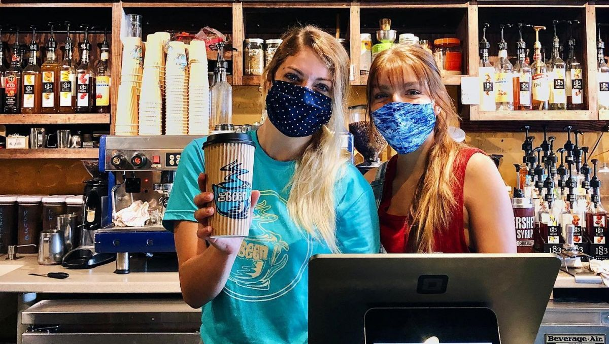 Two women wearing masks and holding up a coffee cup behind the Counter of DeBeen Espresso