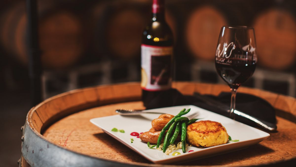 Small plate, glass of wine and wine bottle from Old North State Winery sitting on a wine barrel