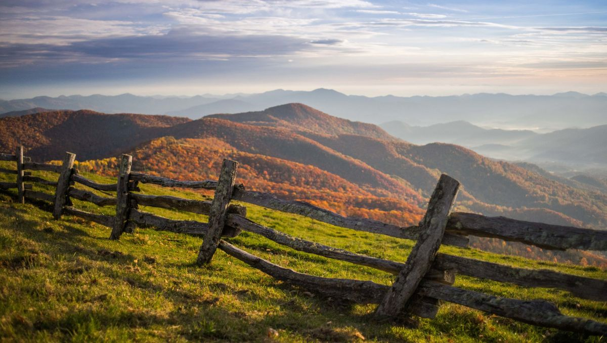 Wood fence with fall foliage and mountains in background at Cataloochee Ranch