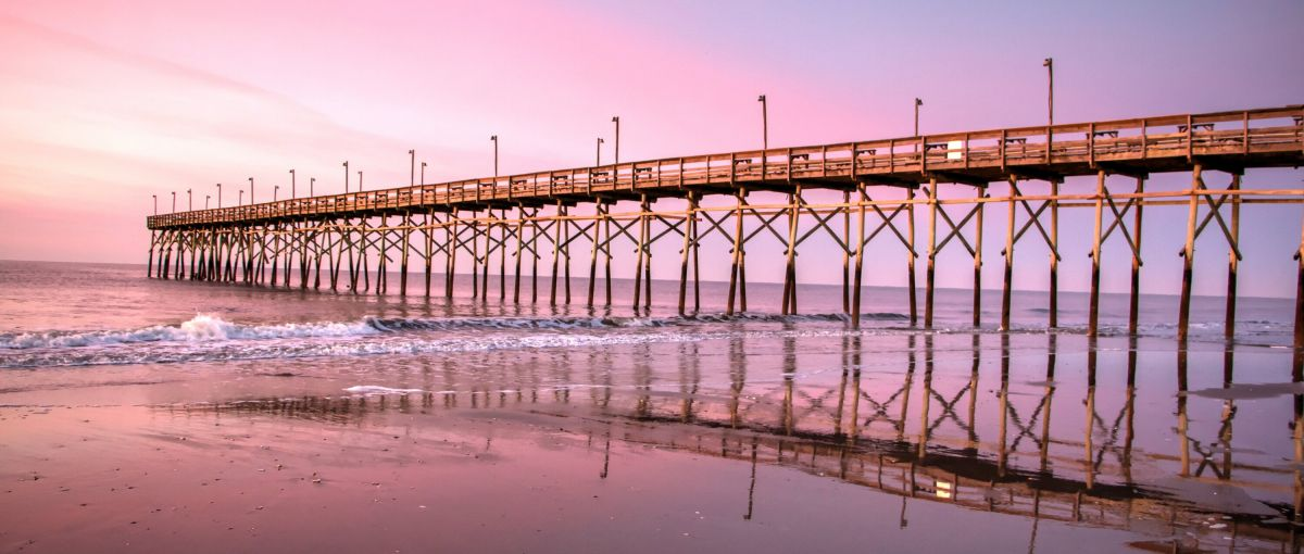 Sunset Beach Pier jutting out into the ocean with pink and purple sky in background