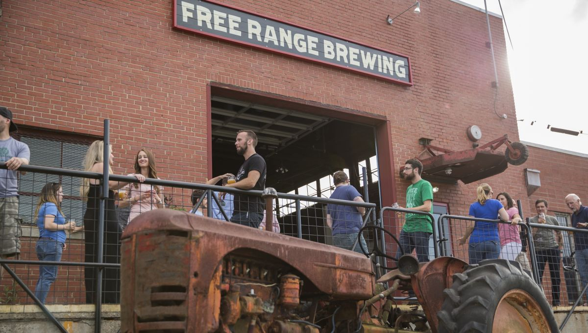 People standing outside Free Range Brewing enjoying beer and talking with a tractor in foreground
