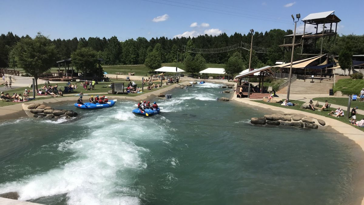 Whitewater rafters on water at U.S. National Whitewater Center with people watching from land on sunny day