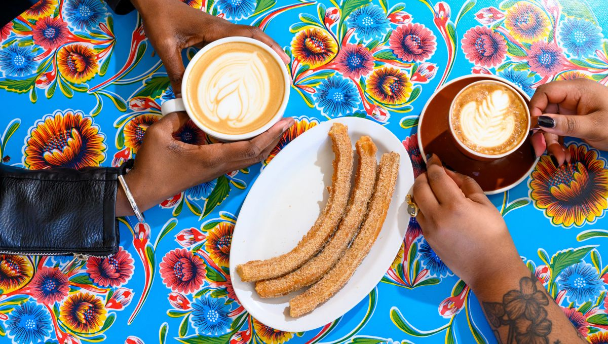 Hands holding cups of coffee with churros in the center of the table