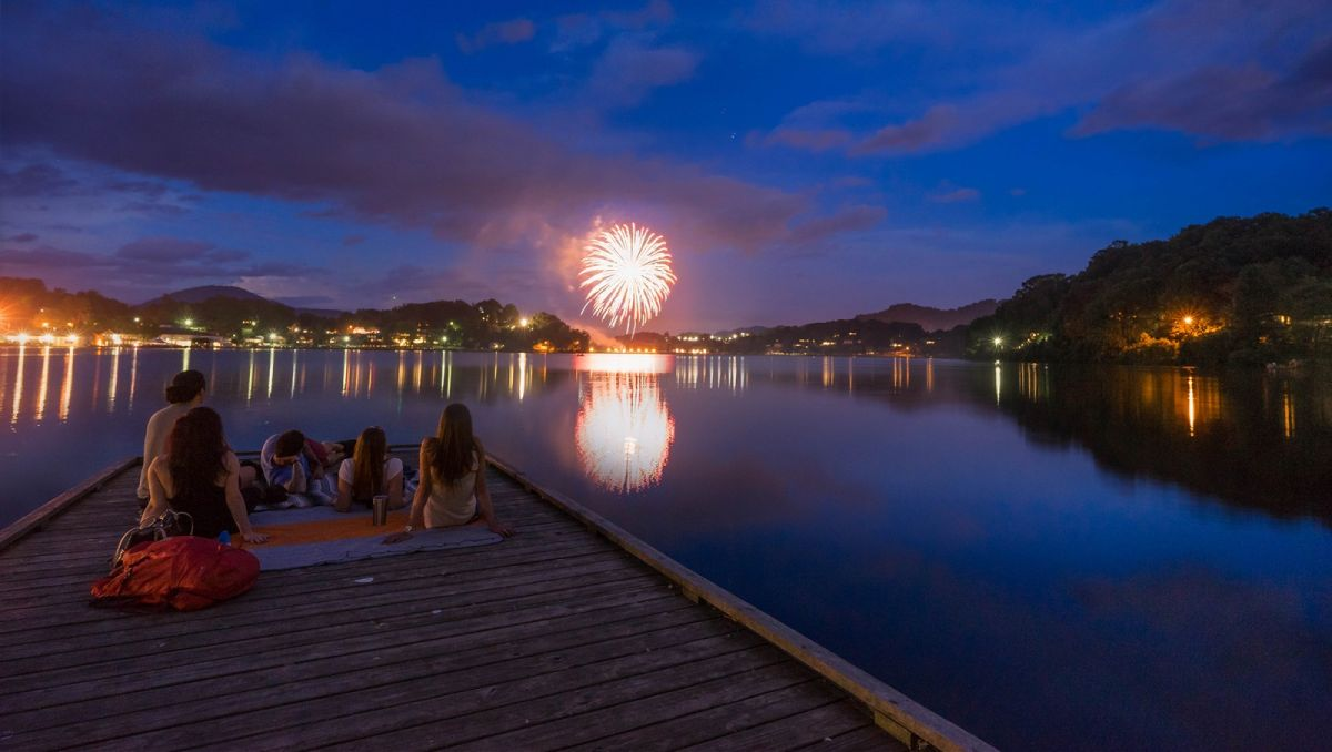 Family on a dock watching fireworks across the lake