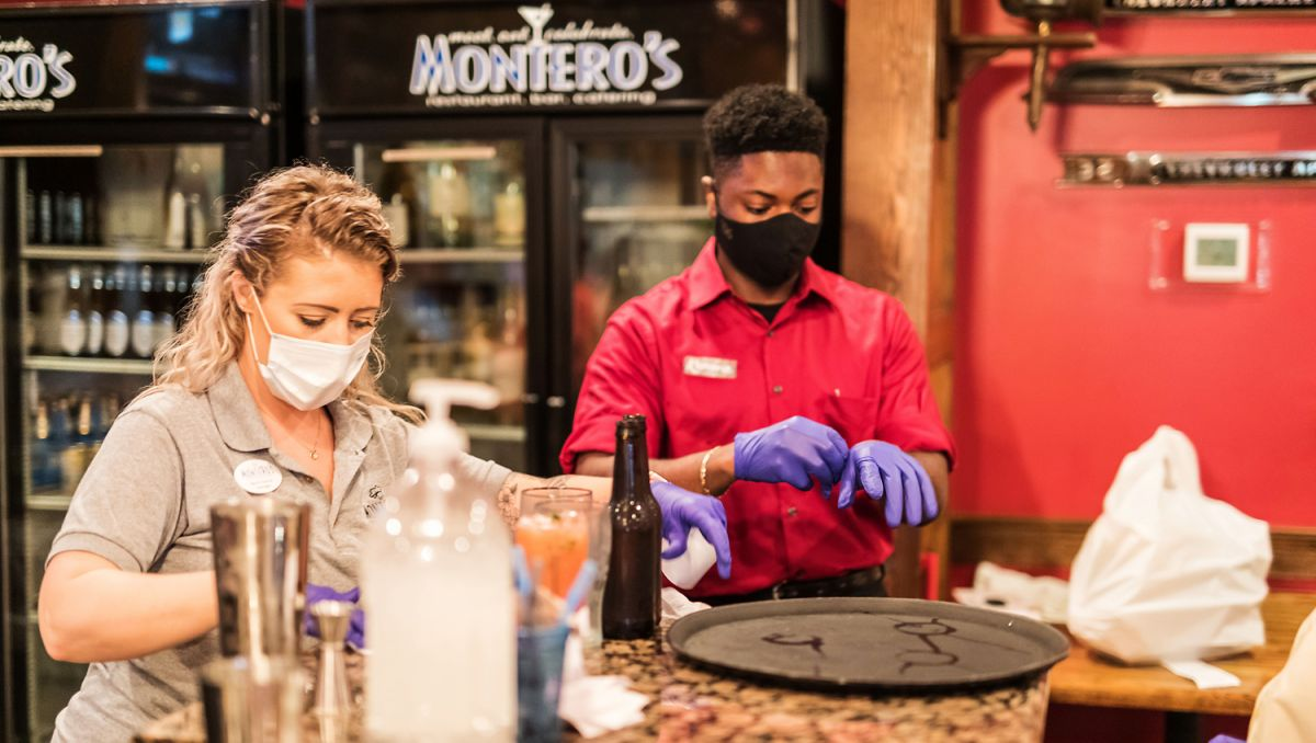 Two employees wearing masks at Montero's Restaurant putting on gloves while standing at bar