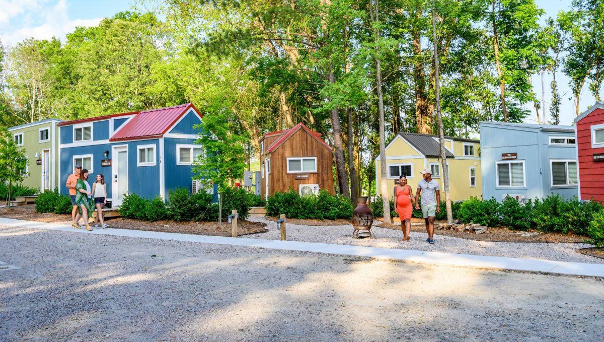 Family and couple walking outside tiny homes in River and Twine, a tiny house hotel, on sunny day