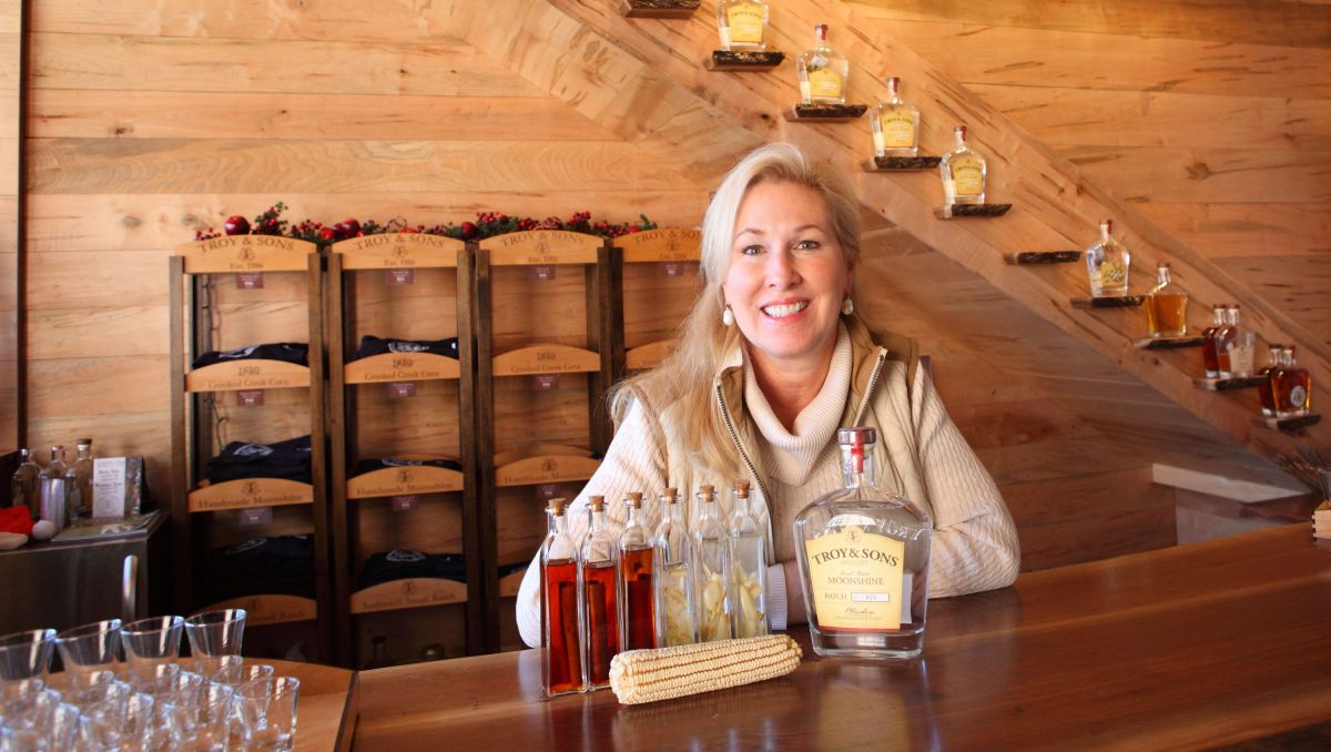 Troy Ball sitting at bar with spirits in front of her at Asheville Distilling