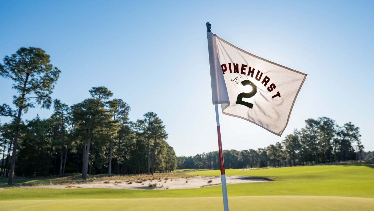 Pinehurst No. 2 flag with course in background on sunny day