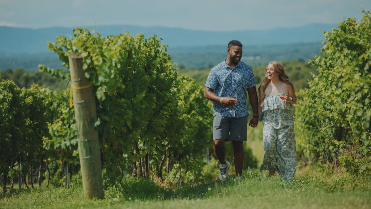 Smiling couple walking hand in hand through Raffaldini Vineyards' vineyard on sunny day