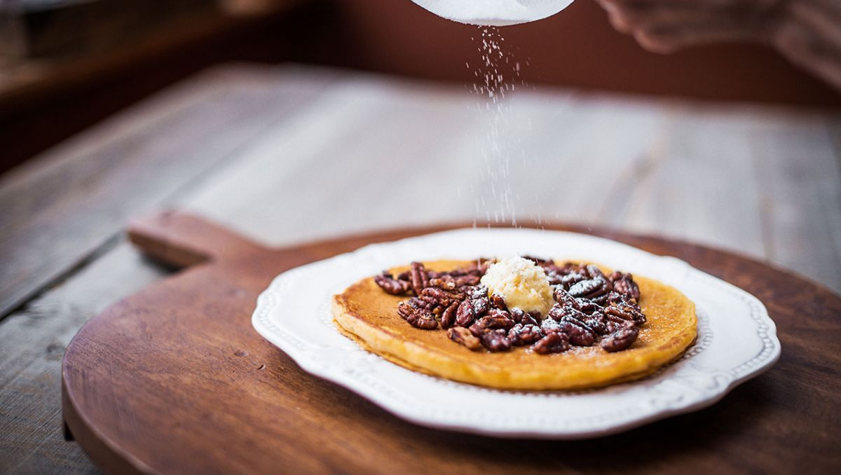 Sweet potato pancake on a serving board with powdered sugar being put on top