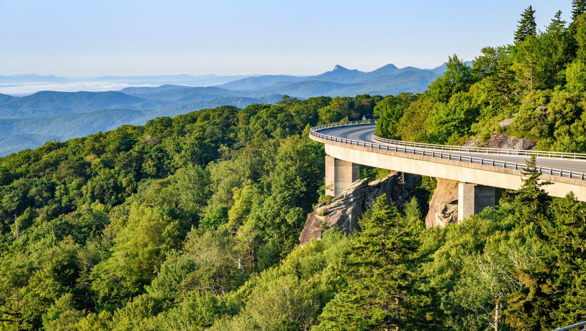 Linn Cove Viaduct to the right with green trees to the left and mountain ridges in background on clear day