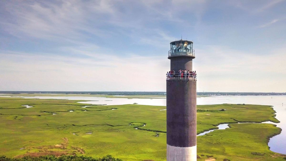 People at the top of Oak Island Lighthouse with marshes in background in Brunswick Islands