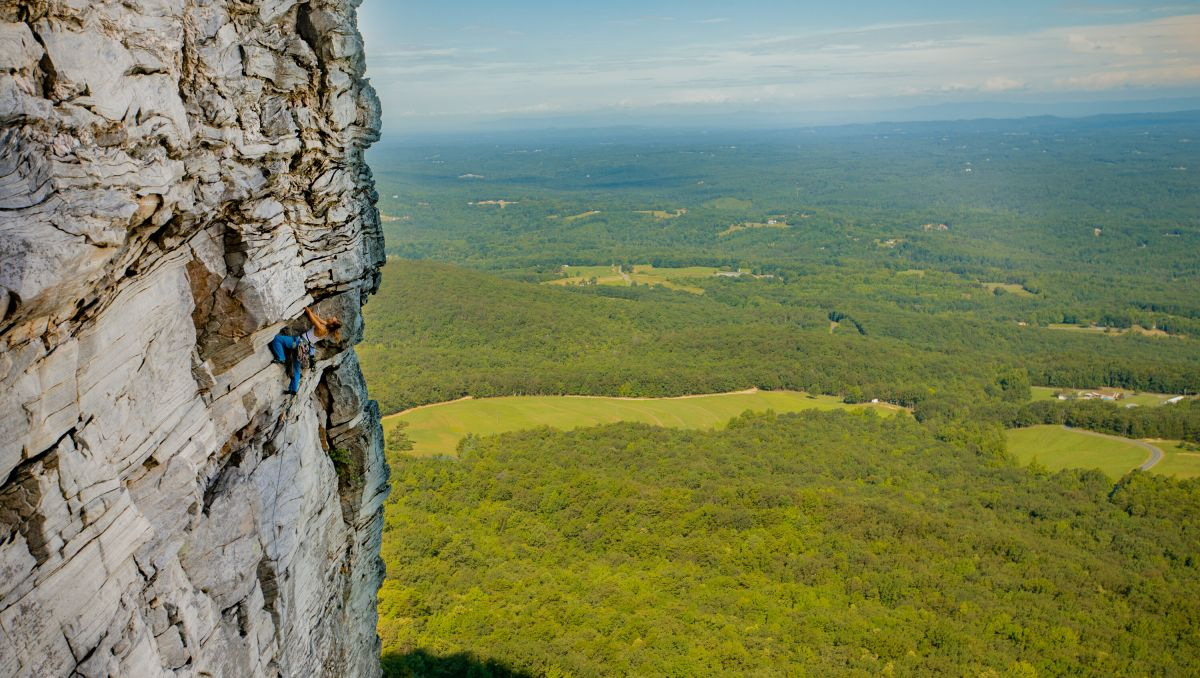 Person climbing cliffs at Hanging Rock State Park with valley below on sunny day