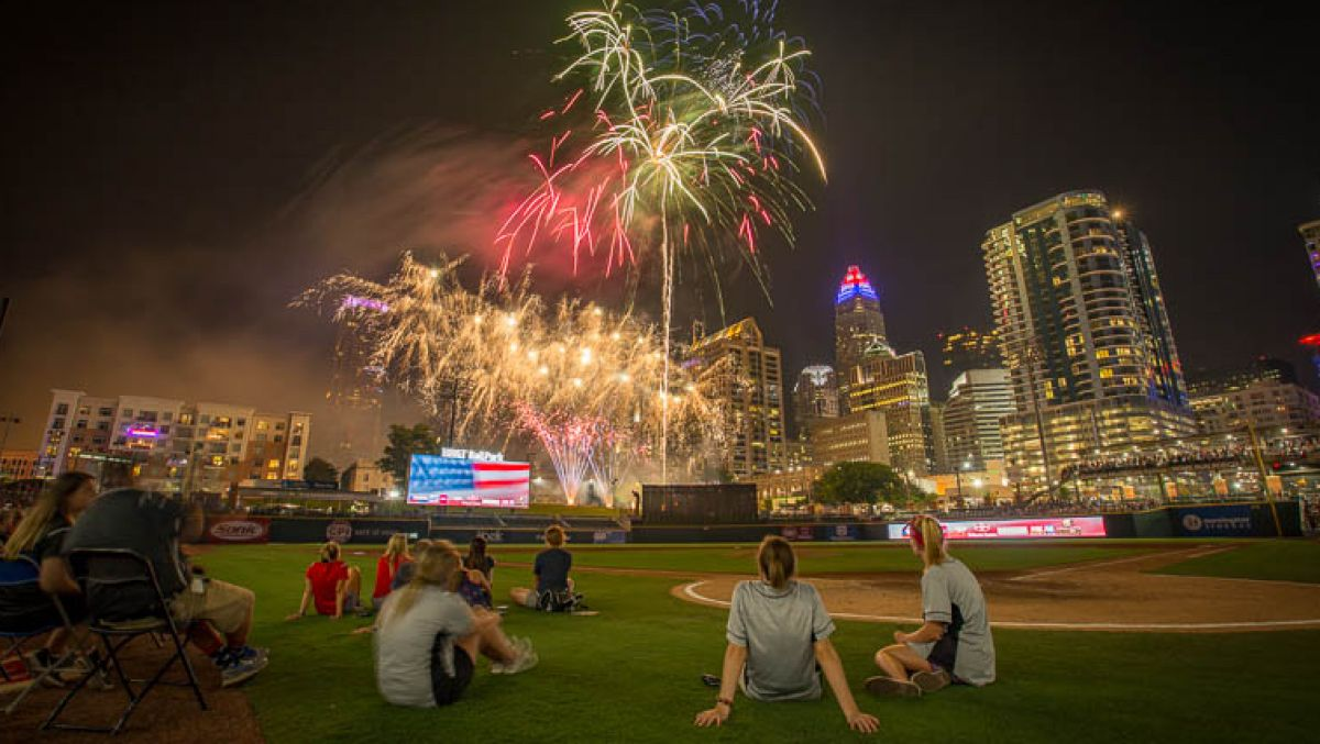 People sitting by home plate on baseball field watching fireworks in sky above Uptown Charlotte