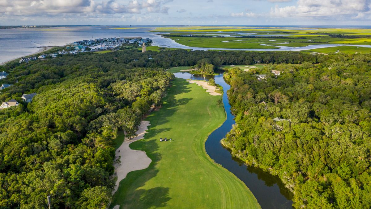 Aerial view of Bald Head Island Golf Club's golf course with trees, Old Baldy and waterways during daytime