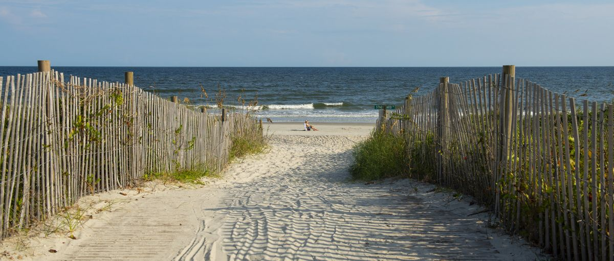 Beach access leading to man sitting on beach with ocean in background in N.C.'s Brunswick Islands