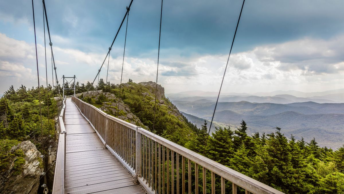 Entrance of Mile High Swinging Bridge with mountains in background during daytime